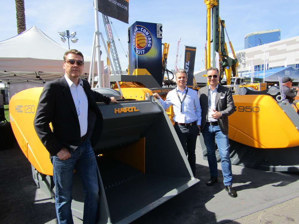 Hartl Crusher North America brought its line of crusher buckets to ConExpo. (L-R): Martin Hartl, vice president; Alexander Hartl, CEO; and Dominic Hartl, president, pose for a photo around their HBC1250 model.