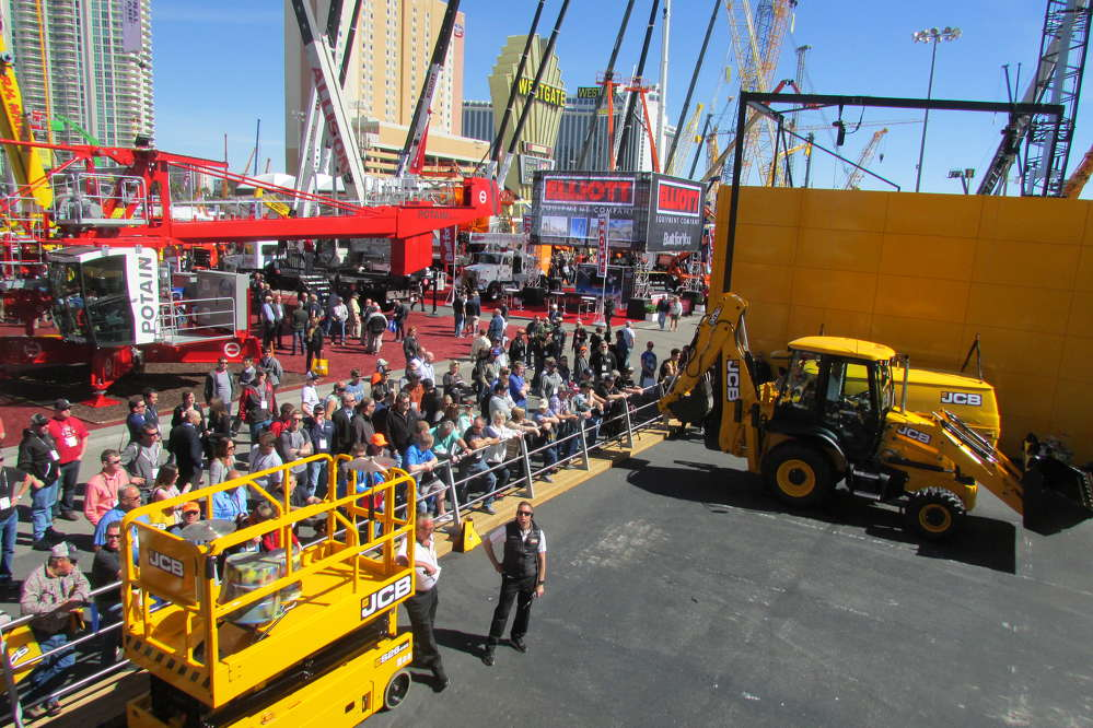 A crowd gathers to watch a demonstration of new JCB equipment at ConExpo.