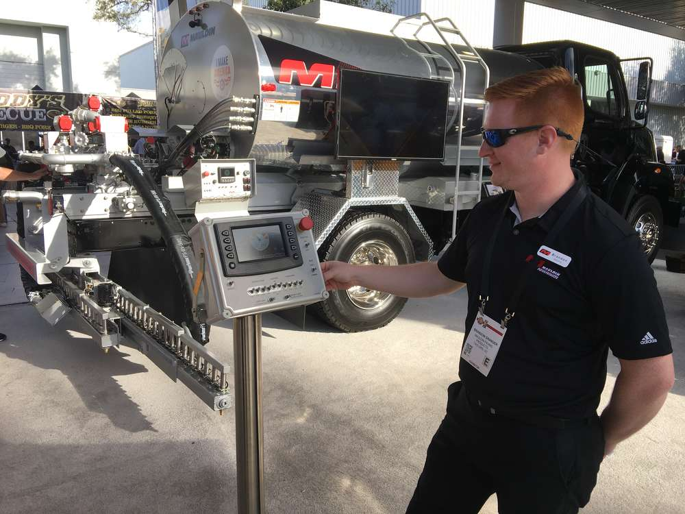 Brandon Granger of Calder Brothers goes over the new user interface in the company's Precision Spray Truck. The interface increases the productivity of the machine by monitoring the outflow of the material, providing instant feedback to the operator.
