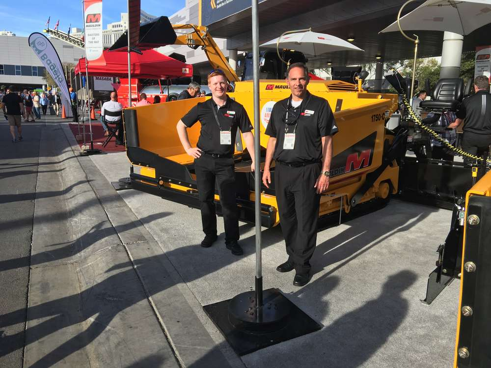 Brandon Granger (L) and Glen Calder, both of Calder Brothers, the manufacturers of  Mauldin Paving Products, stand in front of their popular 1750C paver.