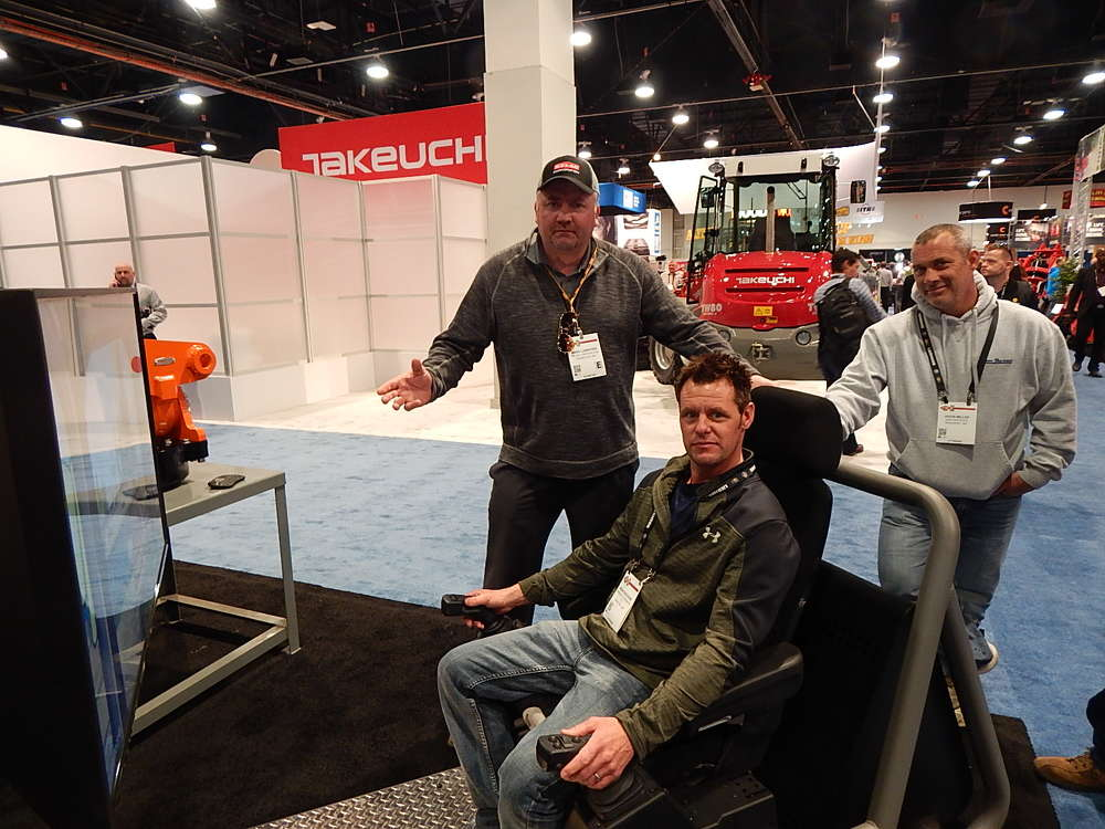 Excavator simulator was a big hit at the Helac booth. (L-R): Mark Lunstead, Helac national sales manager, had MN Roadways' Brian Buesgens give it a shot with his co-worker, Mark Miller looking on