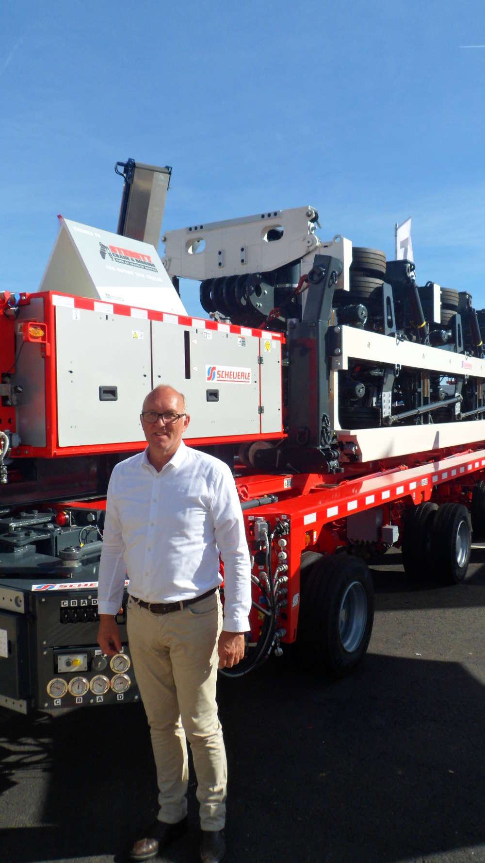(Bernd Schwengsbier, president of TII Sales Group, stands in front of the Scheuerle self-powering trailer.