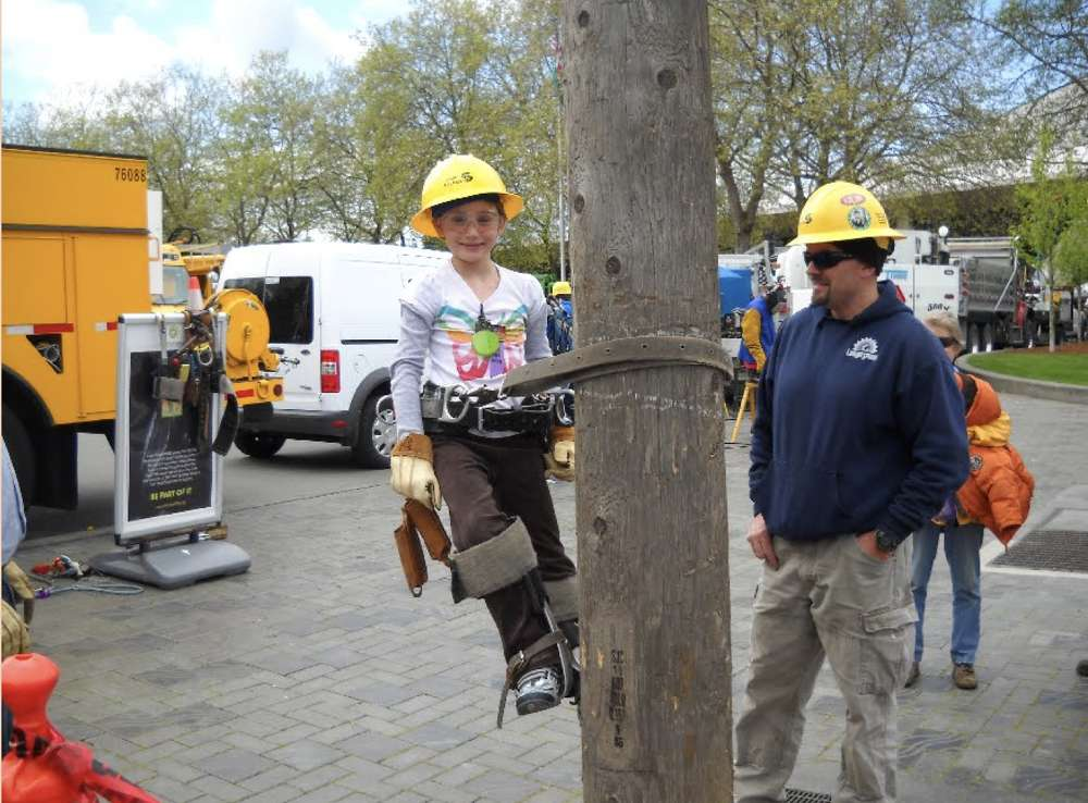 A young attendee at the Washington Women in Trades fair climbs a utility pole.