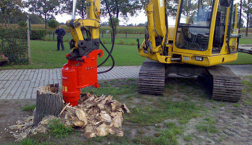 A boom-mounted hydraulic tree stump grinder is attached to a mini excavator to complete the removal of a large, tree stump in a yard space.