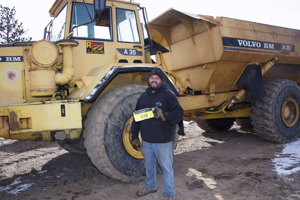Jesse Andreoff of JSA Services in Buffalo, Minn., stands in front of a '94 Volvo A35 off-road truck.