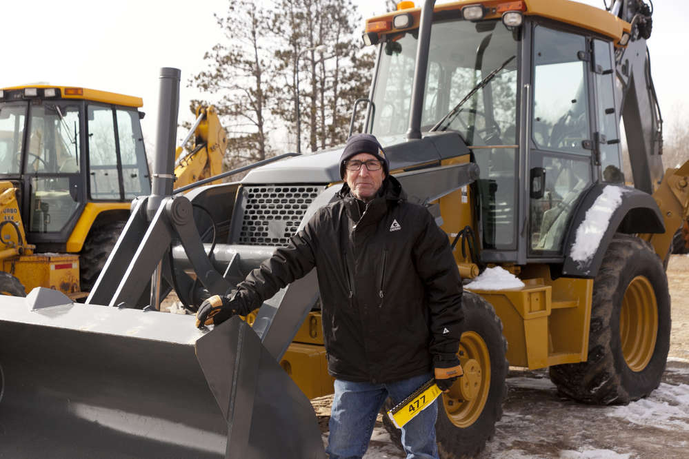 Joseph Leverty of Ogilvie, Minn., inspects this 2008 John Deere 310SJ backhoe