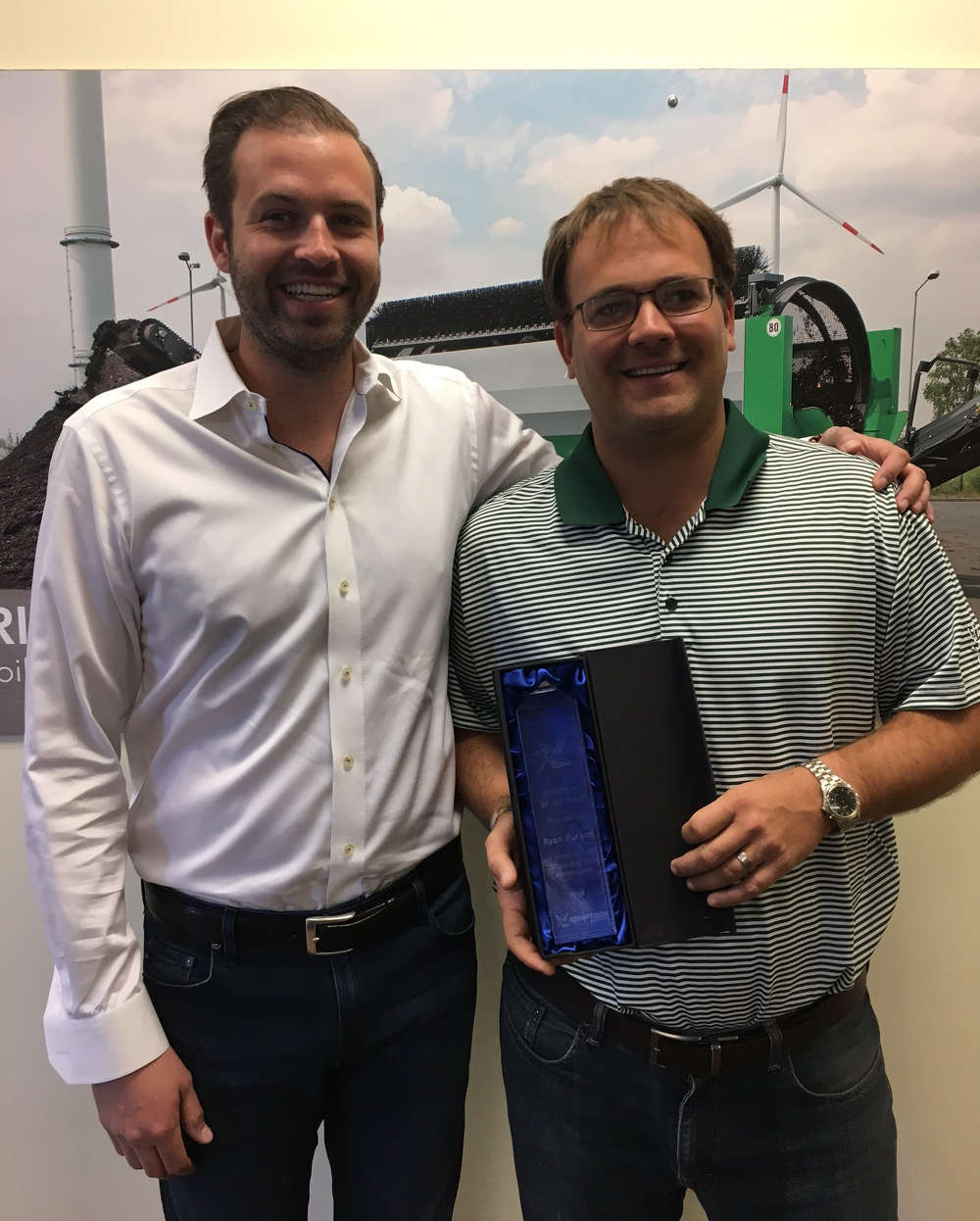 Ryan Puckett (R) from Power Screening, LLC receives the Salesperson of the Year award from Komptech Americas' Brandon Lapsys.