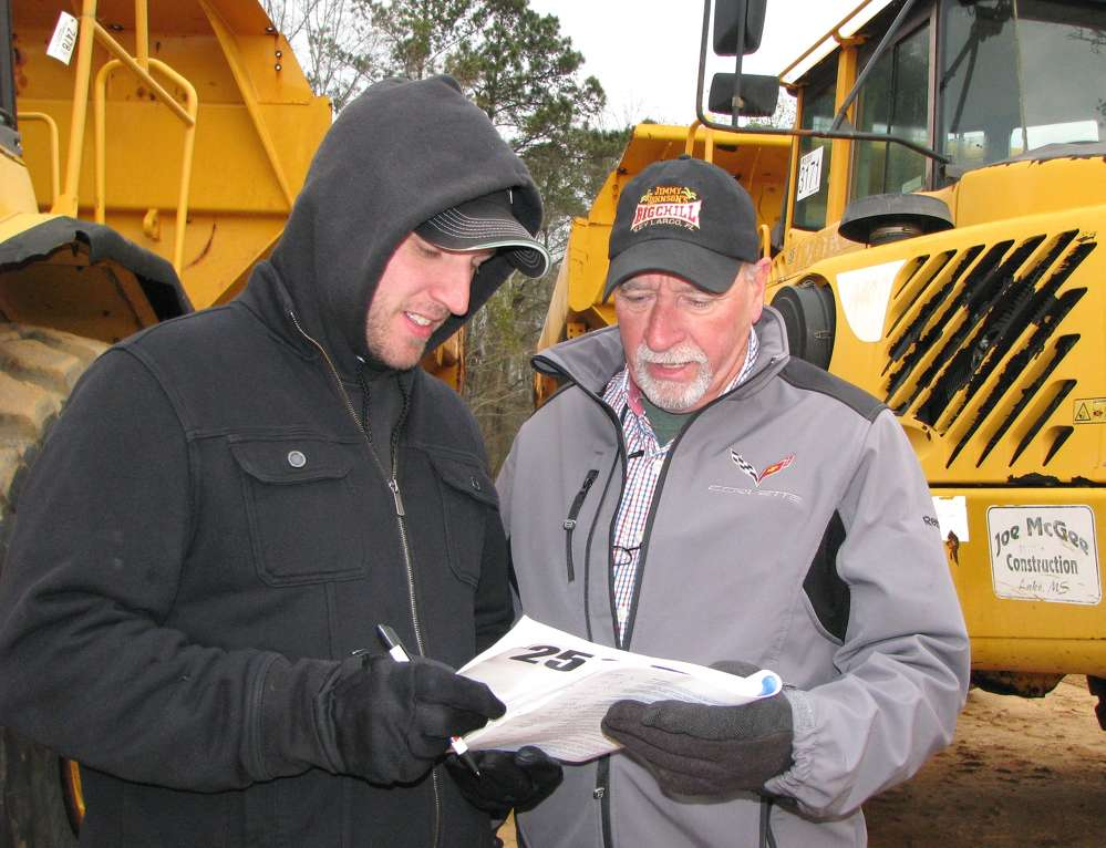 Kevin (L) and Roger McHugh (r) of Brookside Equipment Sales, Phillipston, Mass., look over their notes.