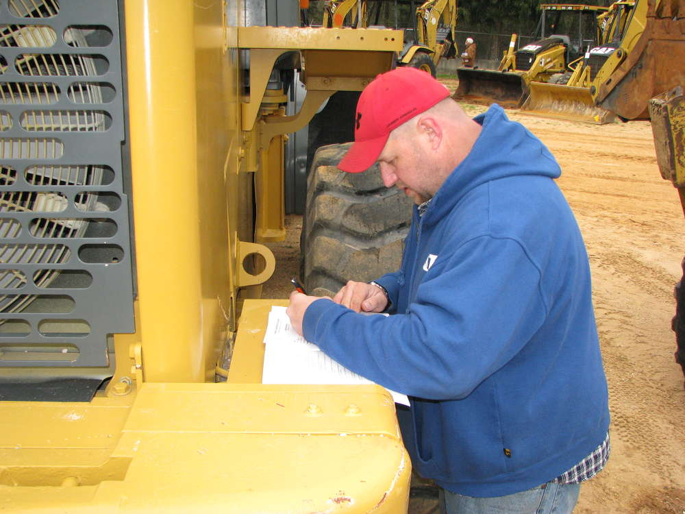 John Bollinger of Pioneer Equipment in Savannah, Ga., takes a break on this John Deere 644J wheel loader to jot a few notes.