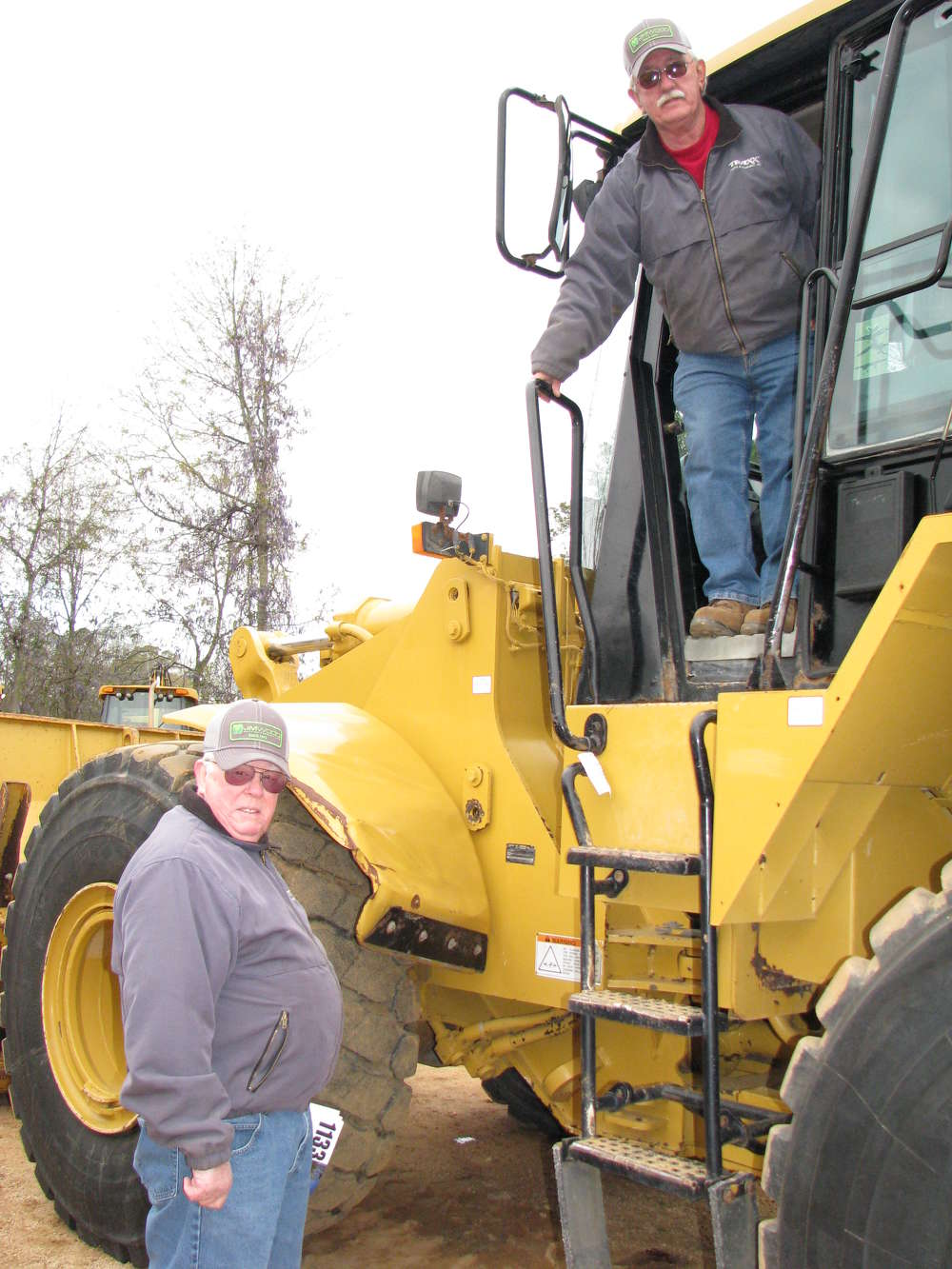 Ed Hallmark (L) and Jerry McLemore of TRAXX Parts & Equipment, Jasper, Ala., climb up on some wheel loaders