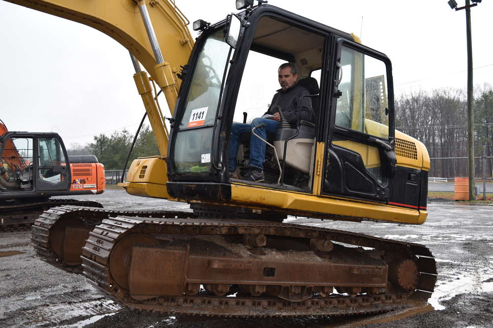 Carlos Garcia of Quinlon Investments in Doral, Fla., tries out this Caterpillar excavator before the bidding begins.