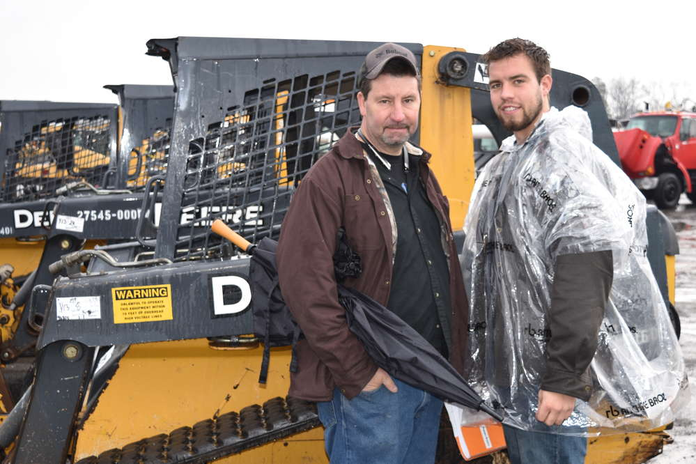 Mark Snyder (L) and Mark Snyder Jr., both owners of Snyder Landscaping in Bernville, Pa., are ready for the rain and the auction.