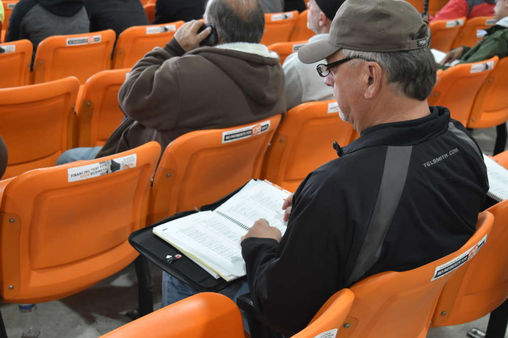 An auction attendee checks his guide to see what was coming up next on the ramp.