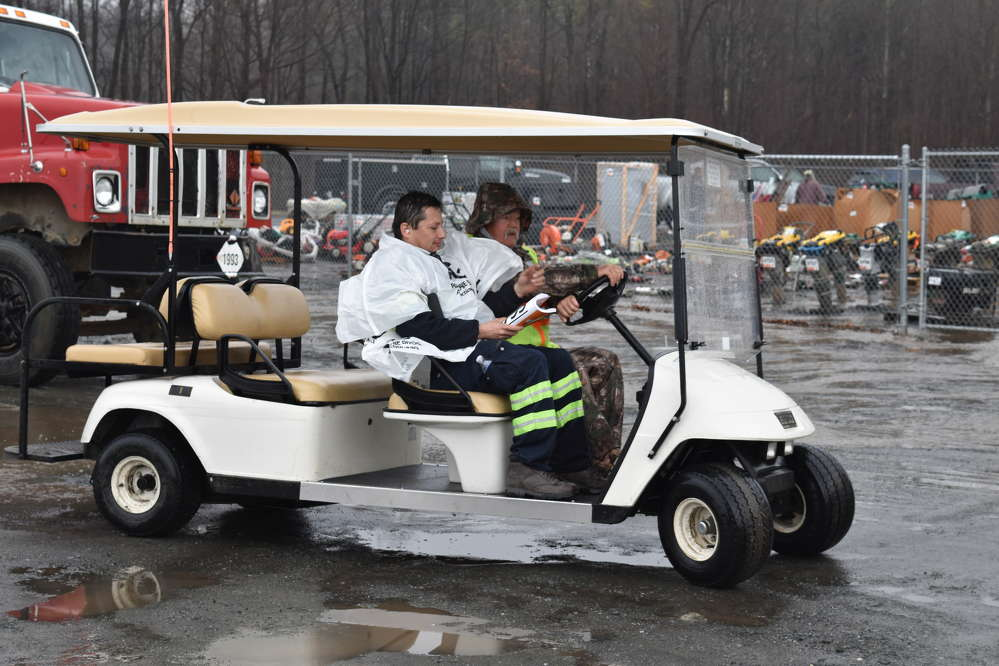 A Ritchie Bros. employee helping shuttle a bidder to view equipment during the heavy rain.