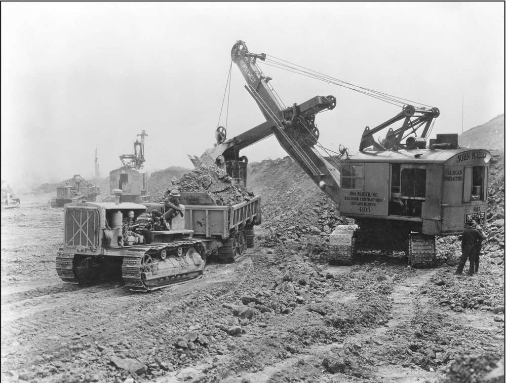 Northwest 80-D shovels loading earth and rock into a fleet of Athey Forged-Trak 2-way dump trailers pulled in tandem by Caterpillar RD-8 diesel tractors.