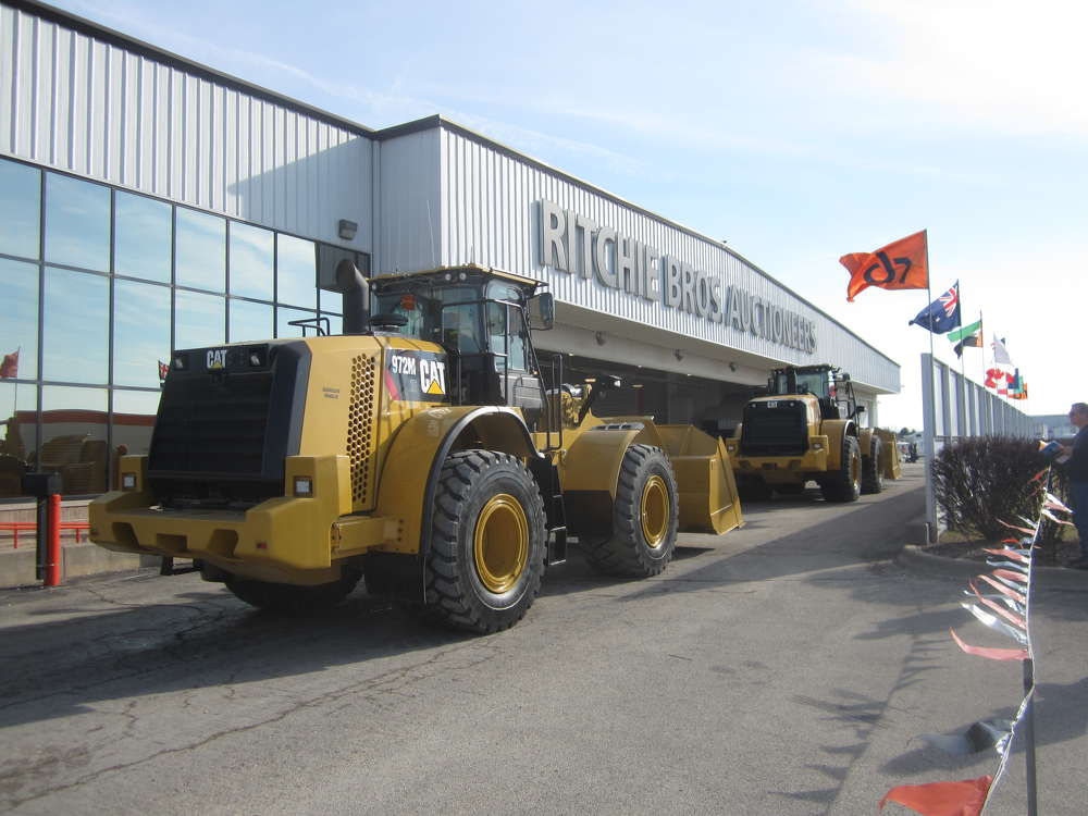 Two late-model Cat 972M wheel loaders roll across the auction ramp.