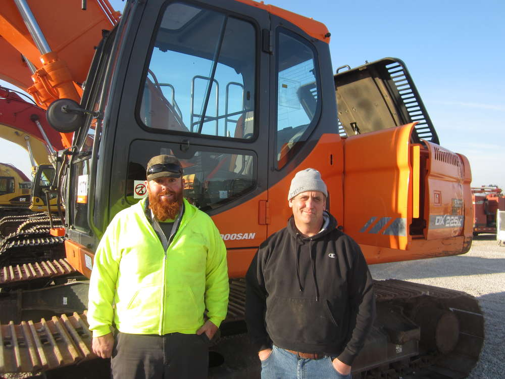 Ed Peters (L) and Ken Ness, both of Express Transport, check out the excavators at the auction.