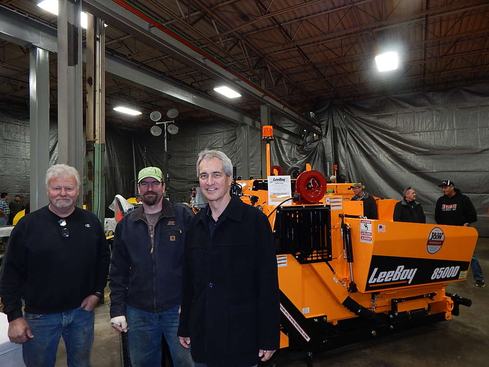 (L-R): Tom Herrmann, head of operations, and Dave Emerton, head of paving, both of J&W Asphalt, Burnsville, Minn., are greeted by Dave Johnson, vice president of marketing of Road Machinery & Supplies, in front of this LeeBoy 8500D.