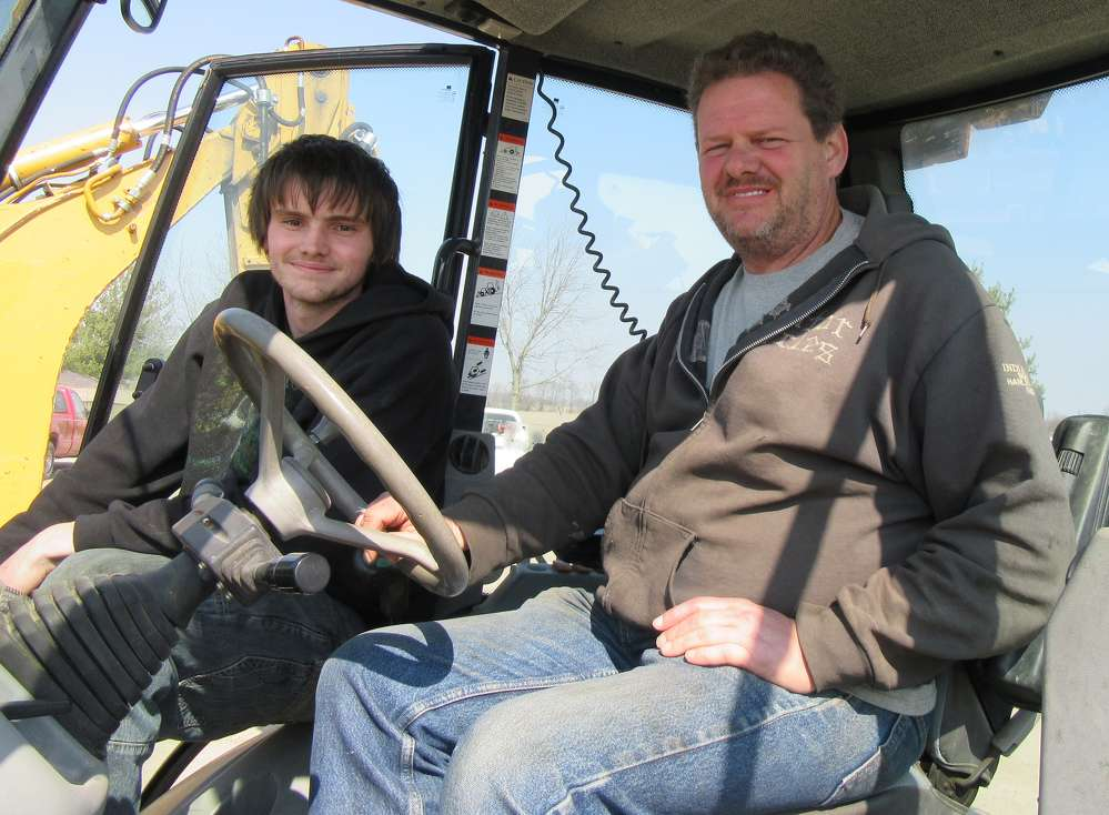 Mackenzie (L) and Scott Brown, both of Brown Farms, Columbus, Ind., check out this Komatsu WB140 backhoe.