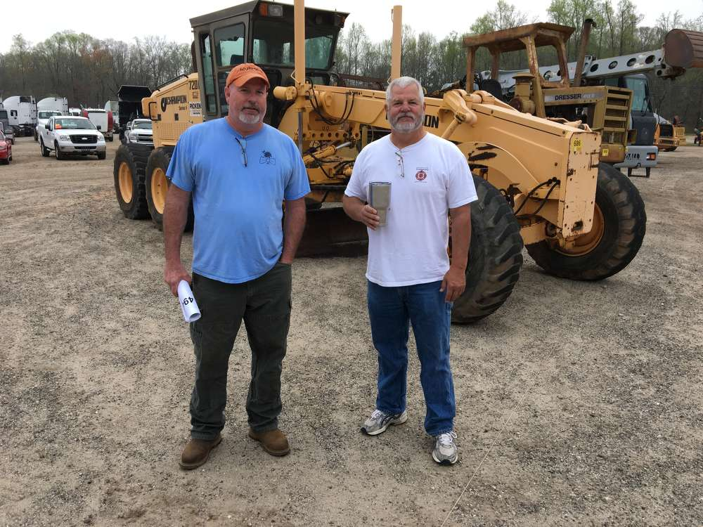 Bryon Sullivan (L) of UTM Enterprises, Gray Court, S.C., and Mark Leverette, Leverette Construction, Gray Court, S.C., consider bidding on this Champion 720A motorgrader.