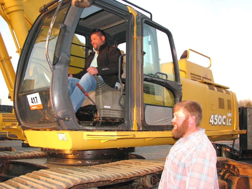 Luke (L) and Josh Smith, independent contractors, Atlanta, Ga., test out this John Deere 450C LC excavator.