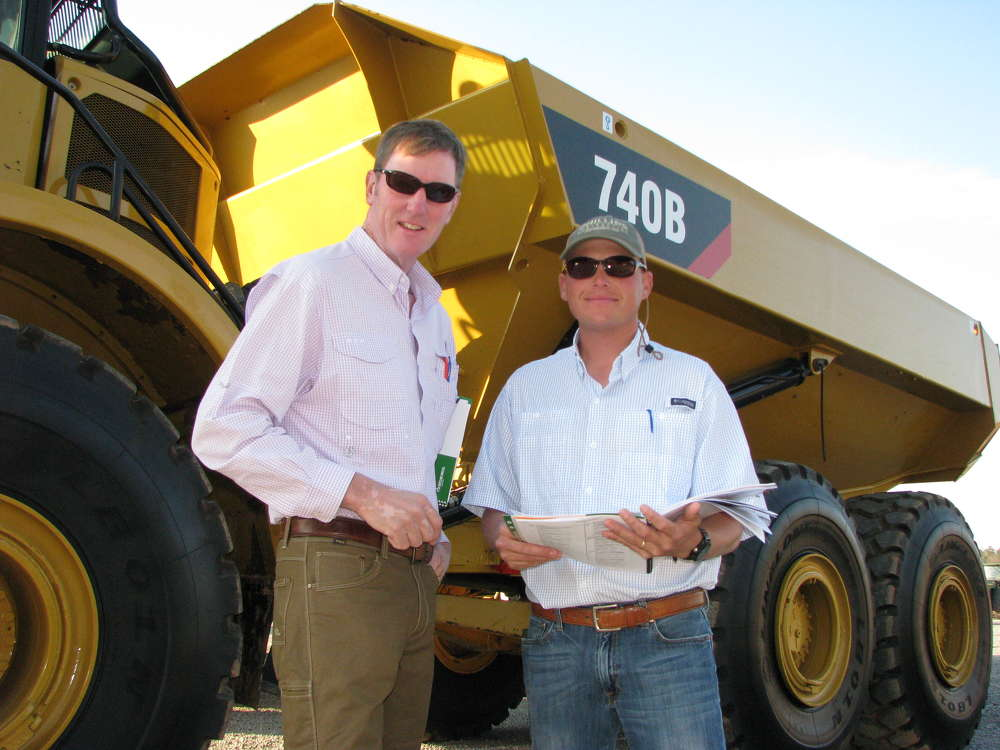 Bobby Lee Phillips (L) and Blake Hill, both of Phillips Contracting Co., Columbus, Miss., compare notes on this Cat 740B artic dump truck.