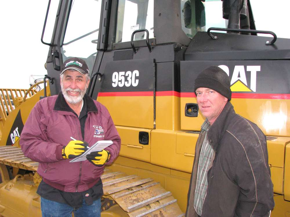 Tim Dellinger (L) and Todd Martin, both of TWD Enterprises, Charlotte, N.C., look over the crawler loaders before they go on the auction block.