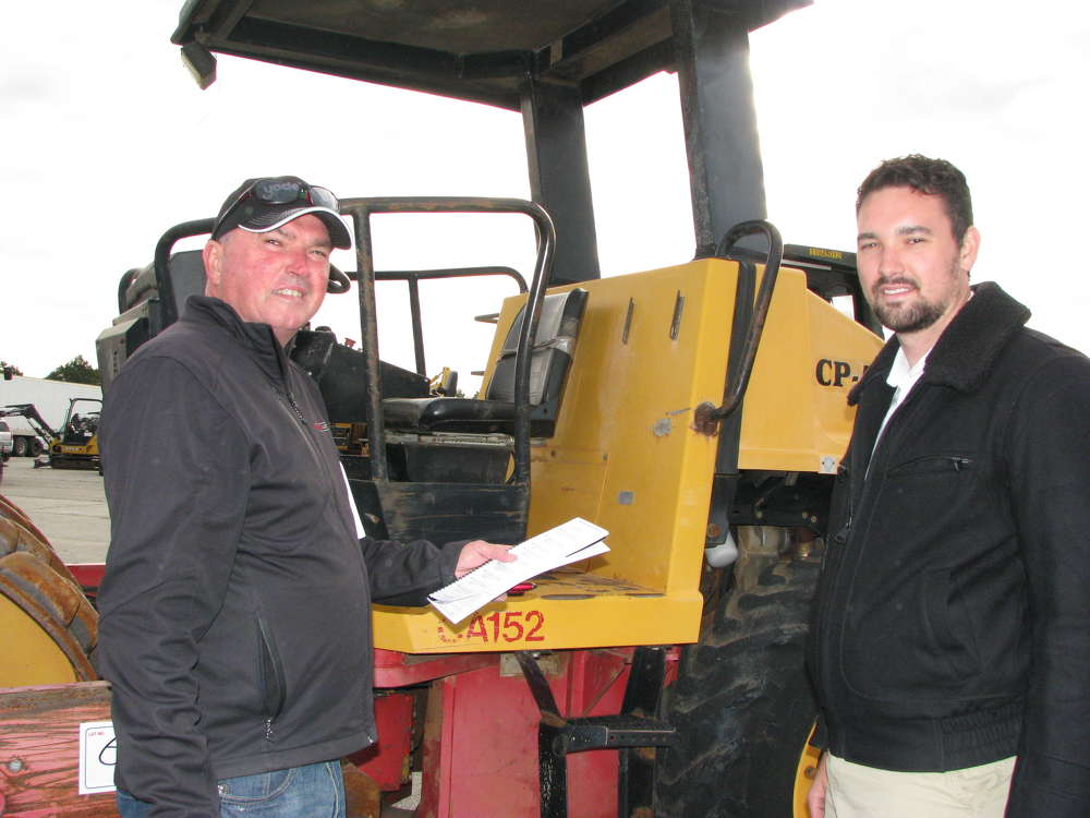 Jimmy Starnes (L) of Drive One, Bessemer, Ala., and Nicolas Starnes of Yoder & Frey Auctioneers discuss the lineup of machines to be auctioned off.