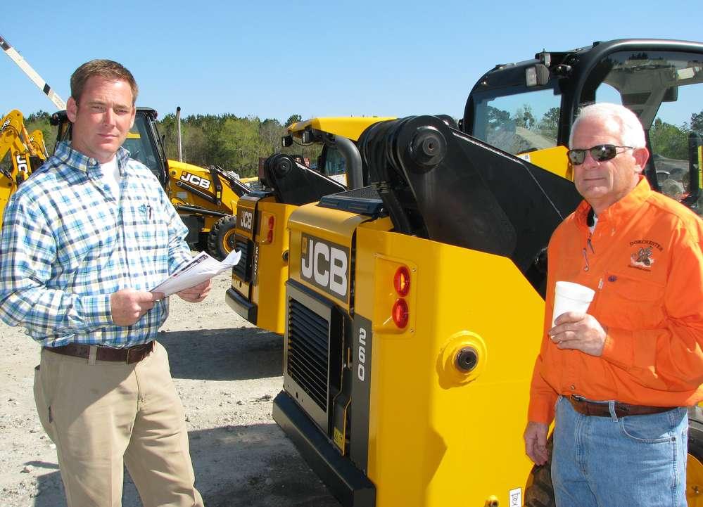 Scott George (L) of Gridiron Parts & Equipment, Pooler, Ga., and Stuart Abel of Stuart Abel Homes, Richmond Hill, Ga., consider bidding on the JCB skid steer loaders and compact track loaders.