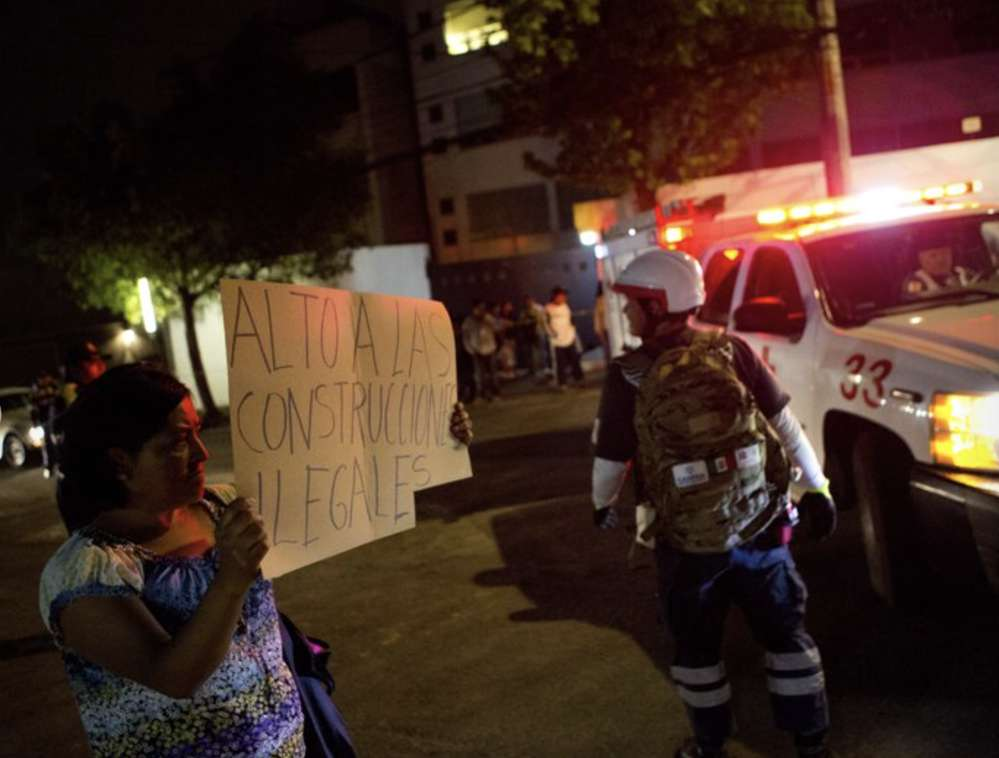 A woman holds a sign that reads