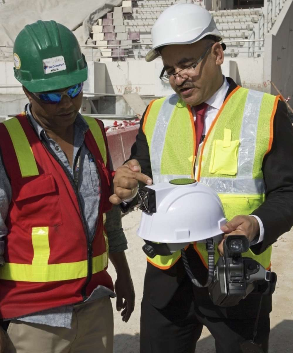 """Dr. Saud Abdul-Aziz Abdul-Ghani, of Qatar University, demonstrates the """"air conditioned"""" hard hat (Supreme Committee for Delivery & Legacy)"""