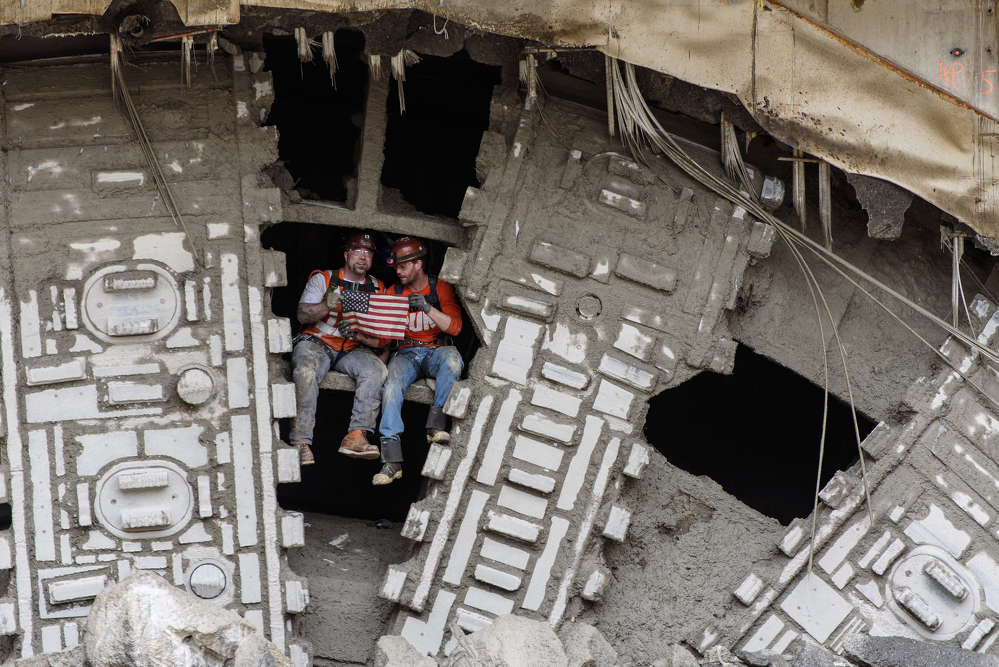 Stars and Stripes for Bertha: Members of Bertha's crew pose with the American flag after the SR 99 tunneling machine broke into her disassembly pit.