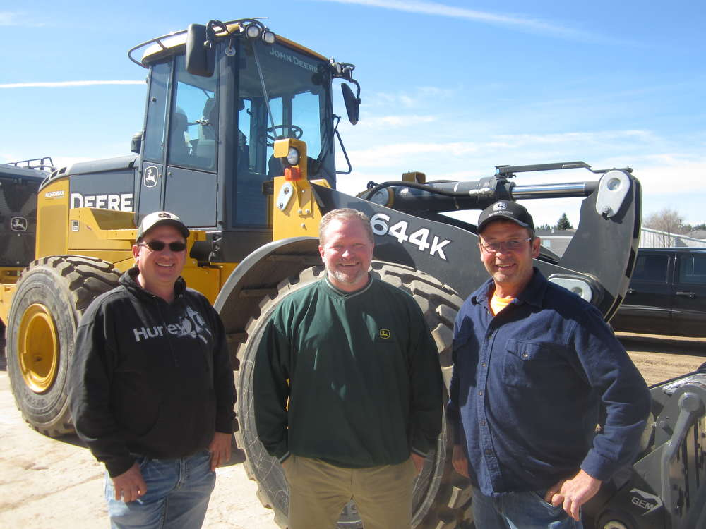 (L-R): Ryan Westaby, owner of Westaby Trucking, Shawn Vetterkind, Nortrax and Steve Sime, S&S Trucking, stand in front of the John Deere 644K wheel loader.