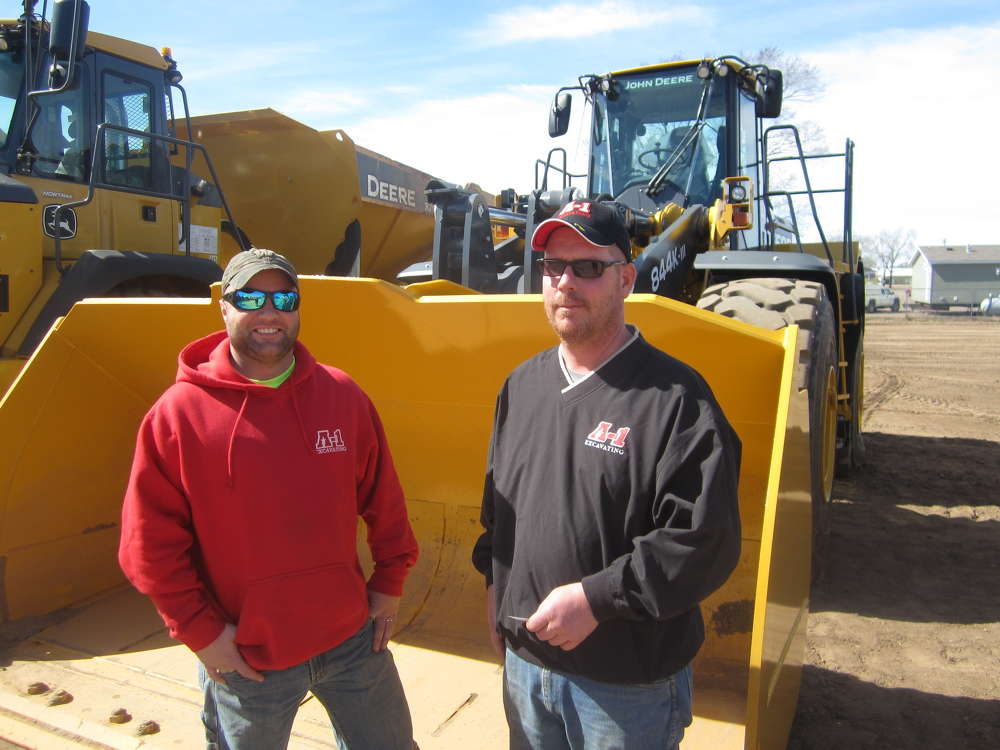 Nate Bleskacek (L) and Doug Johnson, both of A-1 Excavating, check out the bucket of this John Deere 844K wheel loader.