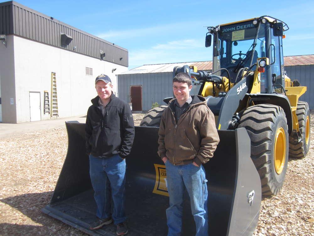 Ryan Burkholder (L) and Elvin Zimmerman, both of Burkholder Tractor, inspect this John Deere certified used 544K wheel loader.