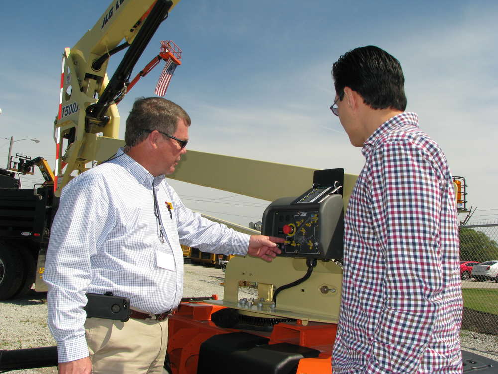 Del Reid (L), Thompson CAT Rental Store salesman,  provides a product demo of a towable JLG T500J boom lift for Hector Lagares of Personnel Placements, Jackson, Tenn.