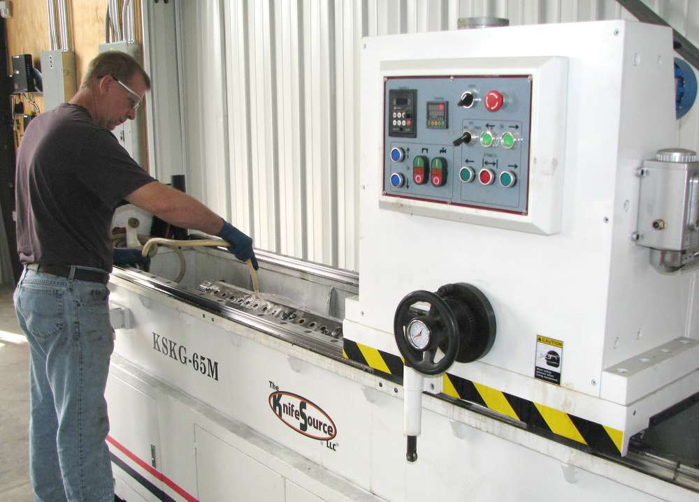 Chris Blackmore, lead service tech, uses a KnifeSource grinding machine for sharpening Bandit chipper knives.