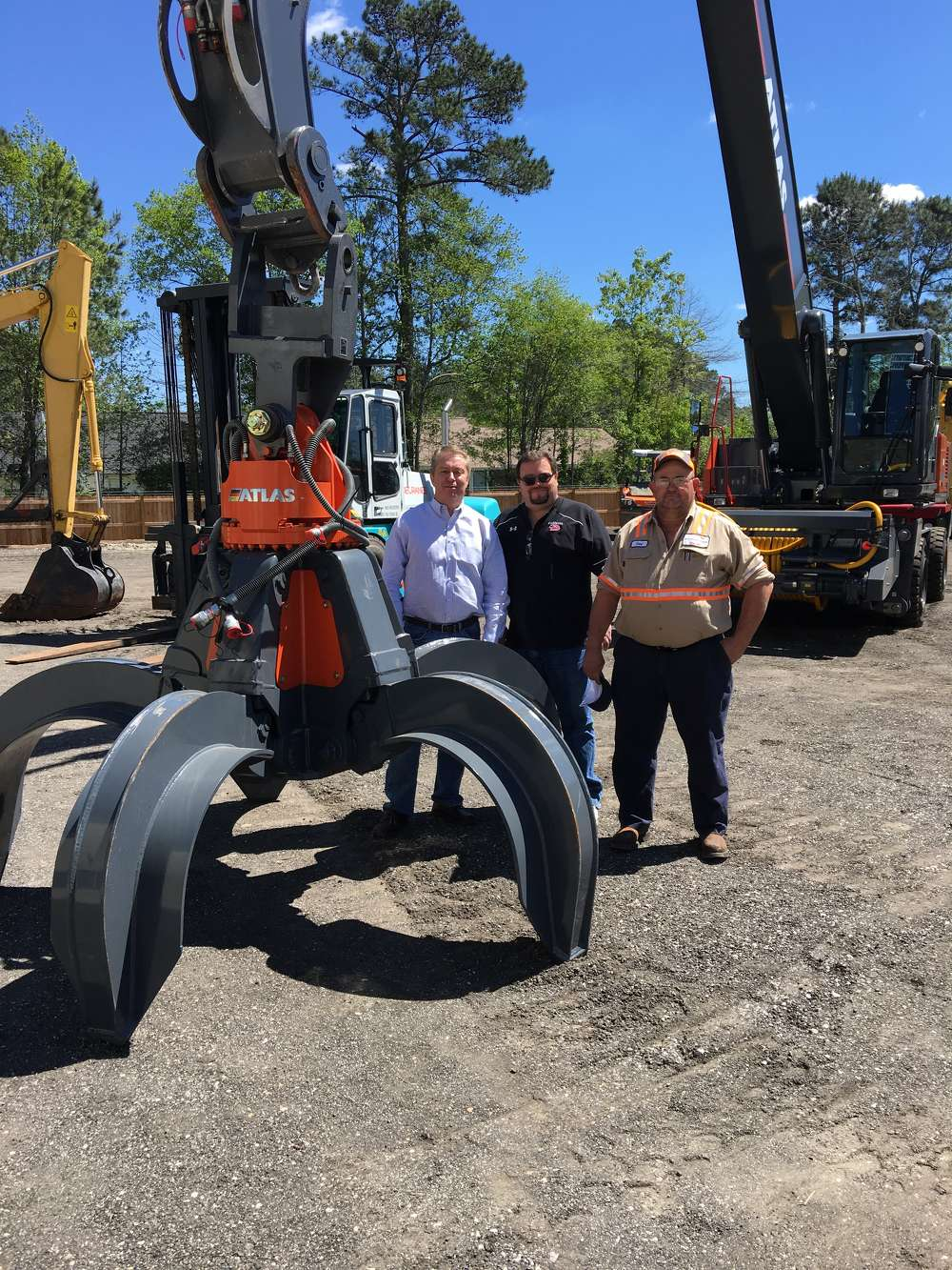 Larry Tracy, Daryne Wall and Earl Thurlow, all of Kinder Morgan Bulk Terminal in Huger, S.C., look over the Atlas 350 material handler.