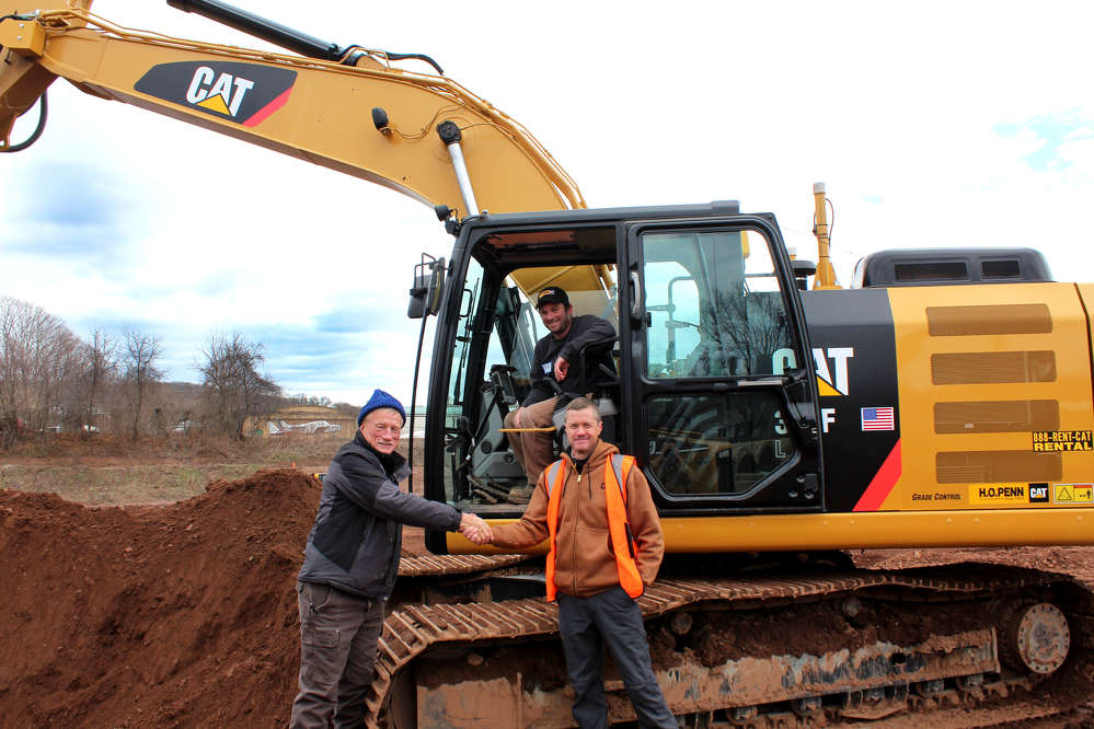 (L-R): Jerry Wilcox Sr. and Jerry Wilcox Jr. of Wilcox Construction seem pleased with the benefits of slope assist on the Cat 323F excavator as explained to them by Tim Schofield of H.O. Penn.