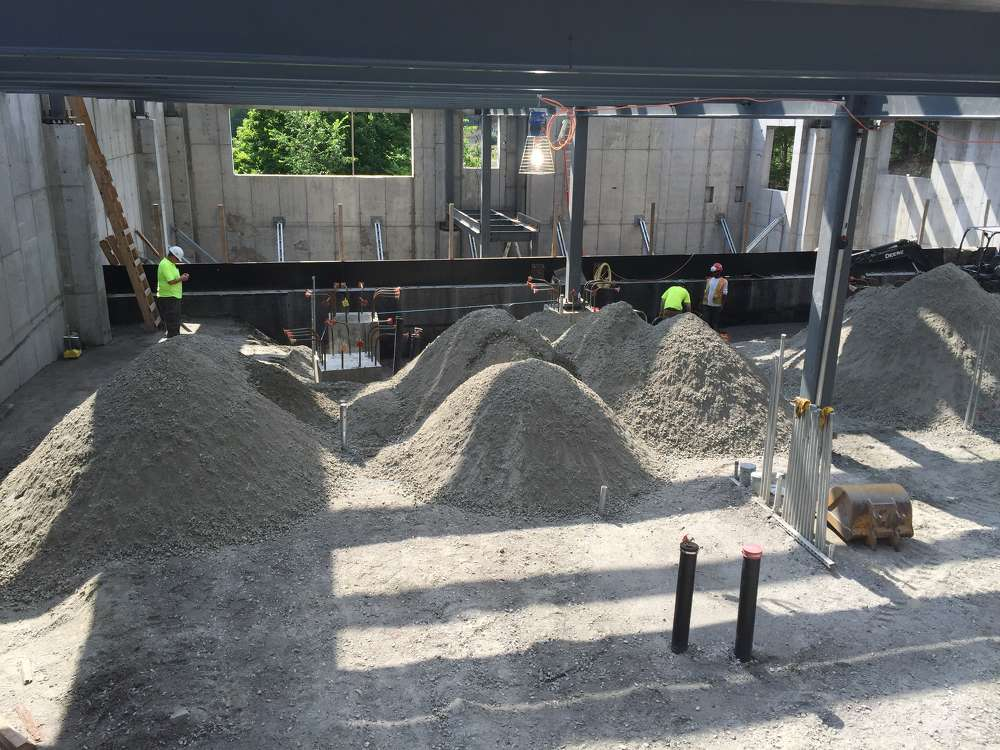 Crews inside the building place and compact the piles of structural fill put in deposited by the Telebelt.