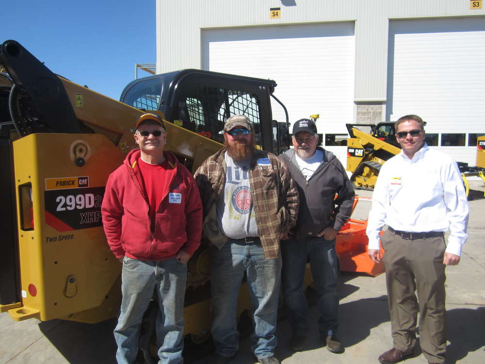 Chris Kline (far R), Fabick CAT, welcomes (L-R) Dave Luedtke and T J Thompson, both of Dave Luedtke Excavating, and Buck Niblett of Buck Niblett Construction to the open house.