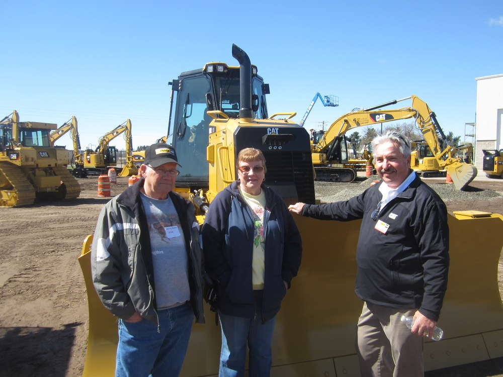 (L-R): Jerry and Marilynn Auman, both of J&M Excavating, talk with Mike Lurndal, Fabick CAT, in front of a Cat D6K dozer.