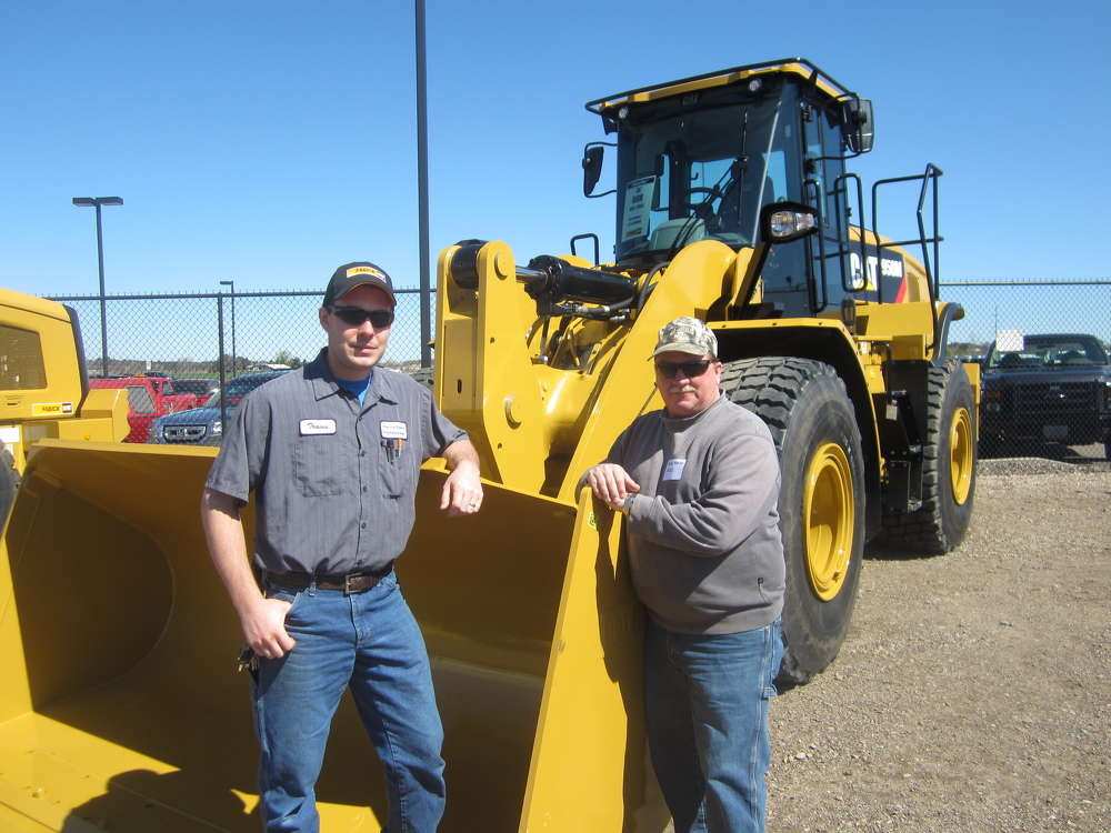 Travis Boyd (L) and Boone Peterson, both of Pierce County, Wis., highway department, check out the Cat wheel loaders.