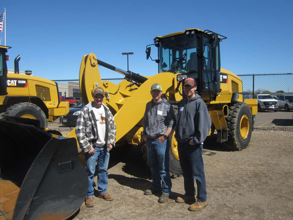 (L-R): Steve Clements, Brent Haglung and Brian Kusilek, all of the Pierce County highway department, stand in front of this Cat 938M wheel loader.