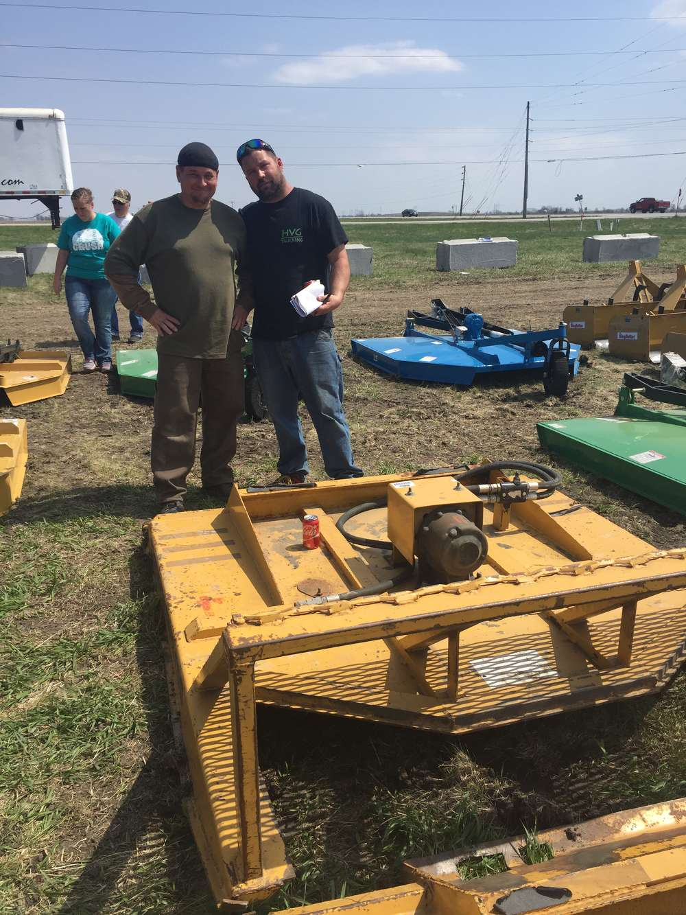 Chad Moret (L) and Josh Gillespie of Des Moines, Iowa, inspect the farm and construction equipment attachments at the Ottumwa, Iowa, auction.