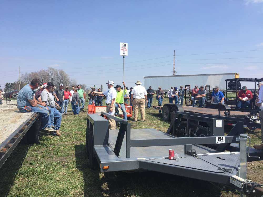 A group of bidders gather to bid on trailers during the April 13 auction in Ottumwa, Iowa.
