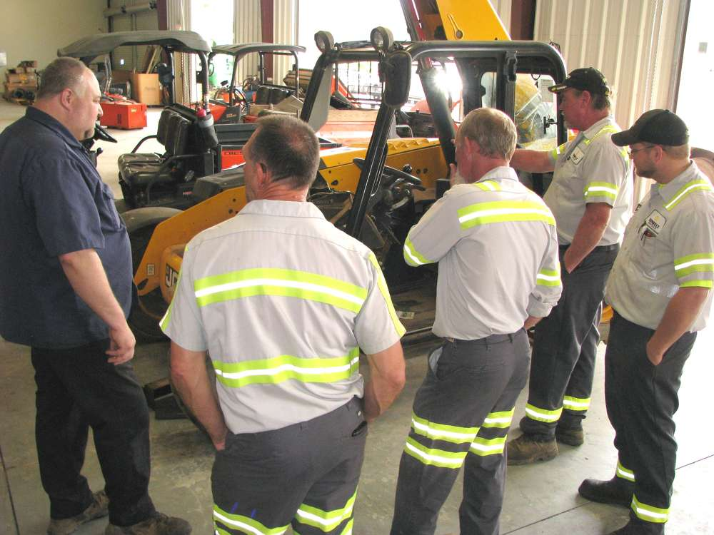 David Nickelson (L), Atlanta JCB service manager, shows a group of attendees around the shop area.