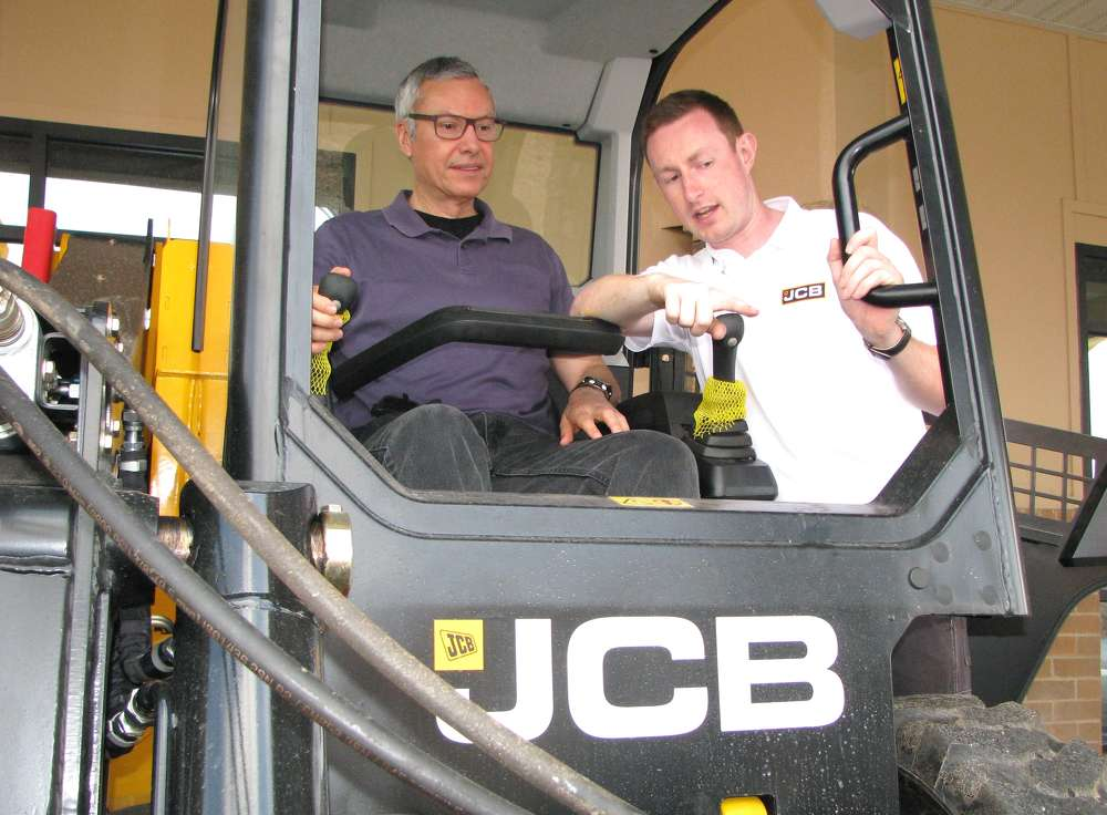 Francisco Tizon (L), international business consultant, Atlanta, Ga., tries out this JCB 225eco skid steer loader with help from Tom Fraser, regional product specialist,  JCB.