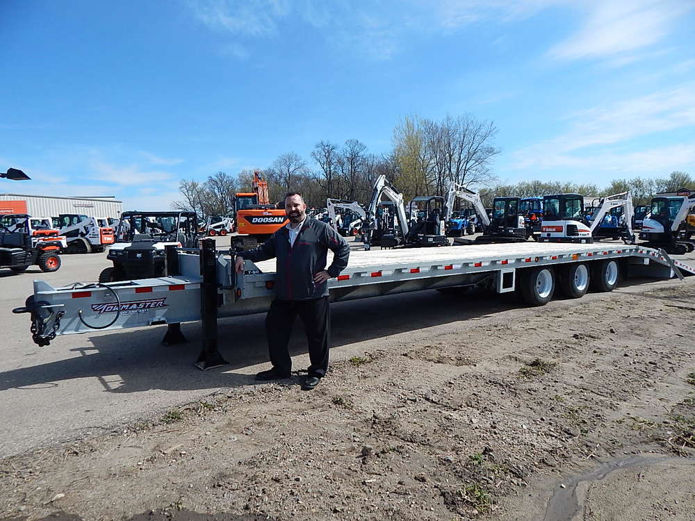 Bob Pace, territory sales representative of Towmaster, Litchfield, Minn., stands with the company's T-50 galvanized trailer with a 50,000-lb. capacity, 28-ft. hydraulic deck.