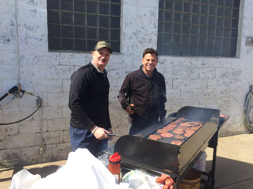Eric Grube (L), Bobcat district service manager, mans the grill with Tim Krahn, senior manager, dealer accounts, Bobcat Company, West Fargo, N.D.